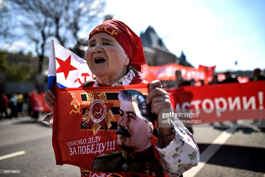 A Russian Communist party activist carries a banner with an image of late Soviet leader Joseph Stalin during a May Day rally in central Moscow on May 1, 2016. / AFP / KIRILL