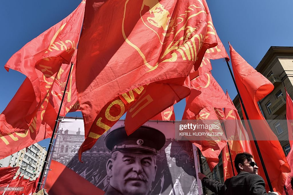A Russian Communist party activist holds a red flag as he stands next to a banner with a portrait of late Soviet leader Joseph Stalin during a May Day rally in central Moscow on May 1, 2016. / AFP / KIRILL