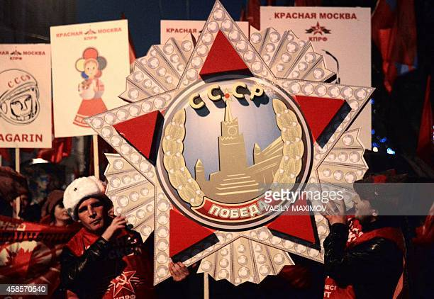 Russian communist party activists hold a model of the main soviet military order of Victory during a rally to mark the 97th anniversary of the 1917...