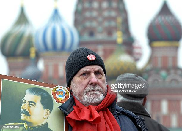 A Russian Communist party supporter holds a portrait of Soviet dictator Joseph Stalin as he takes part in a memorial ceremony to mark the 62nd...