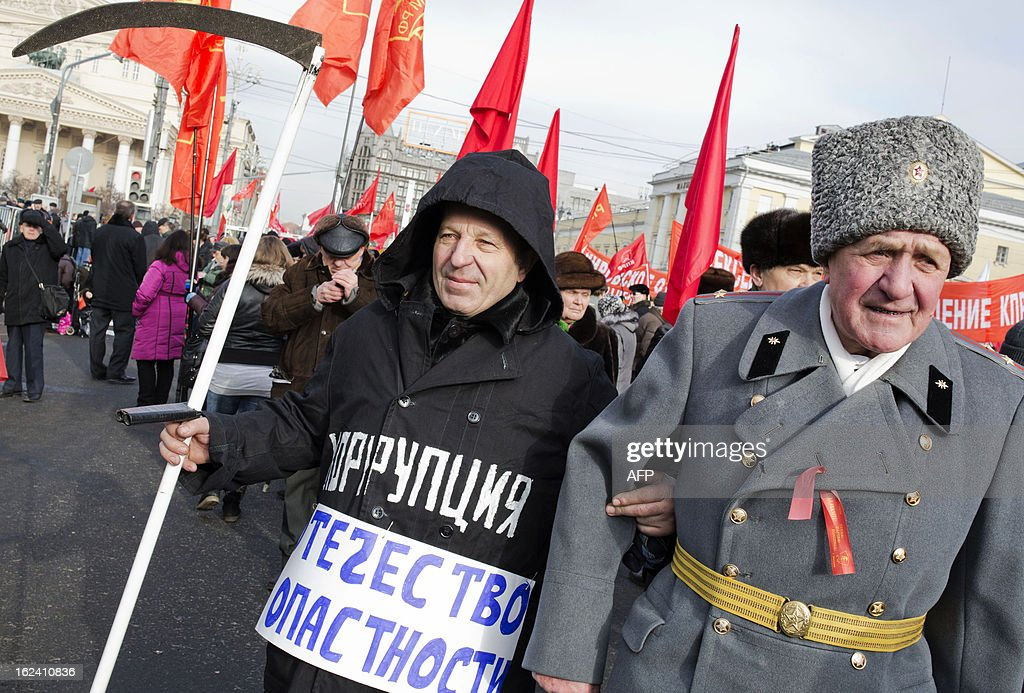 A Russian communist party supporter with inscription on his outerwear reading 'Corruption - Fatherland in danger!' holds a scythe as he walks next to a veteran during a rally devoted to the Defenders of the Fatherland day holiday in Moscow, on February 23, 2013. The Defenders of the Fatherland Day, celebrated in Russia on February 23, honors the nation's military and is a nationwide holiday.