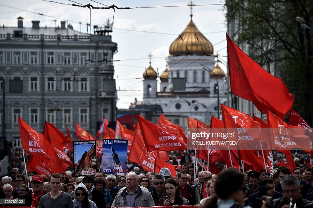 Russian Communist party supporters attend a May Day rally, with the Christ the Savior Cathedral seen in the background, in central Moscow on May 1, 2016. / AFP / KIRILL