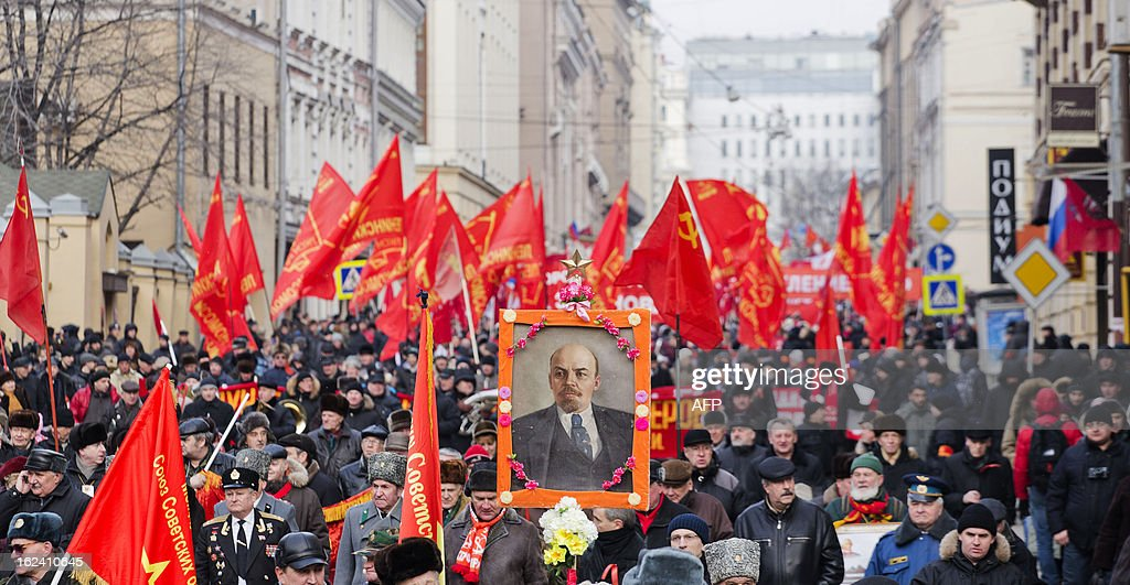 Russian communist party supporters carry red flags and a picture of Vladimir Illitch Lenin during a rally devoted to the Defenders of the Fatherland day holiday in Moscow, on February 23, 2013. The Defenders of the Fatherland Day, celebrated in Russia on February 23, honors the nation's military and is a nationwide holiday. AFP PHOTO / EVGENY FELDMAN