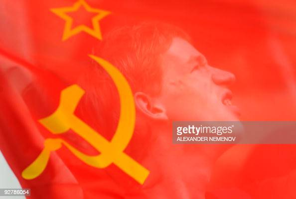 Russian communist protestor is seen through the Soviet flag during a protest in front of a US Embassy in Moscow on August 7 2009 Few hundred of...