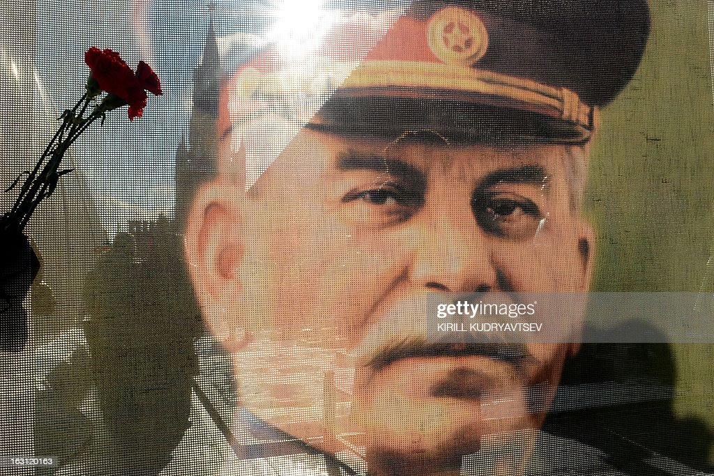 Russian Communists and their supporters are seen through a transparent portrait of Soviet dictator Josef Stalin as they lay flowers at his tomb at the Red Square in Moscow on March 5, 2013, to mark the 60th anniversary of Stalin's death. Russia marks today 60 years since the death of Stalin with attitudes split about whether to view him as a tyrant who slaughtered millions or a national saviour who helped turn the country into a global superpower that emerged victorious in World War II. AFP PHOTO / KIRILL KUDRYAVTSEV