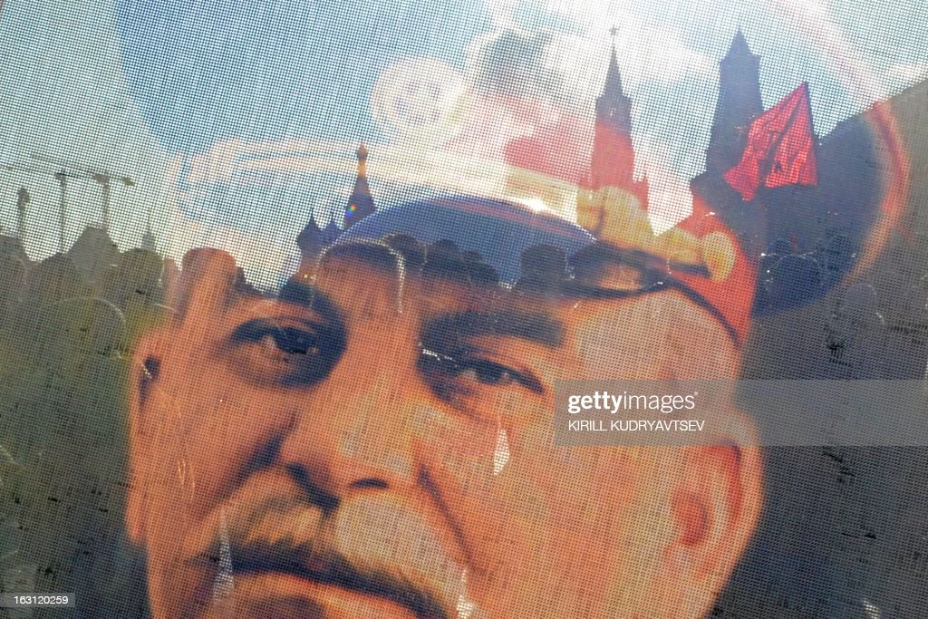 Russian Communists and their supporters are seen through a transparent portrait of Soviet dictator Josef Stalin as they lay flowers at his tomb at the Red Square in Moscow on March 5, 2013, to mark the 60th anniversary of Stalin's death. Russia marks today 60 years since the death of Stalin with attitudes split about whether to view him as a tyrant who slaughtered millions or a national saviour who helped turn the country into a global superpower that emerged victorious in World War II.
