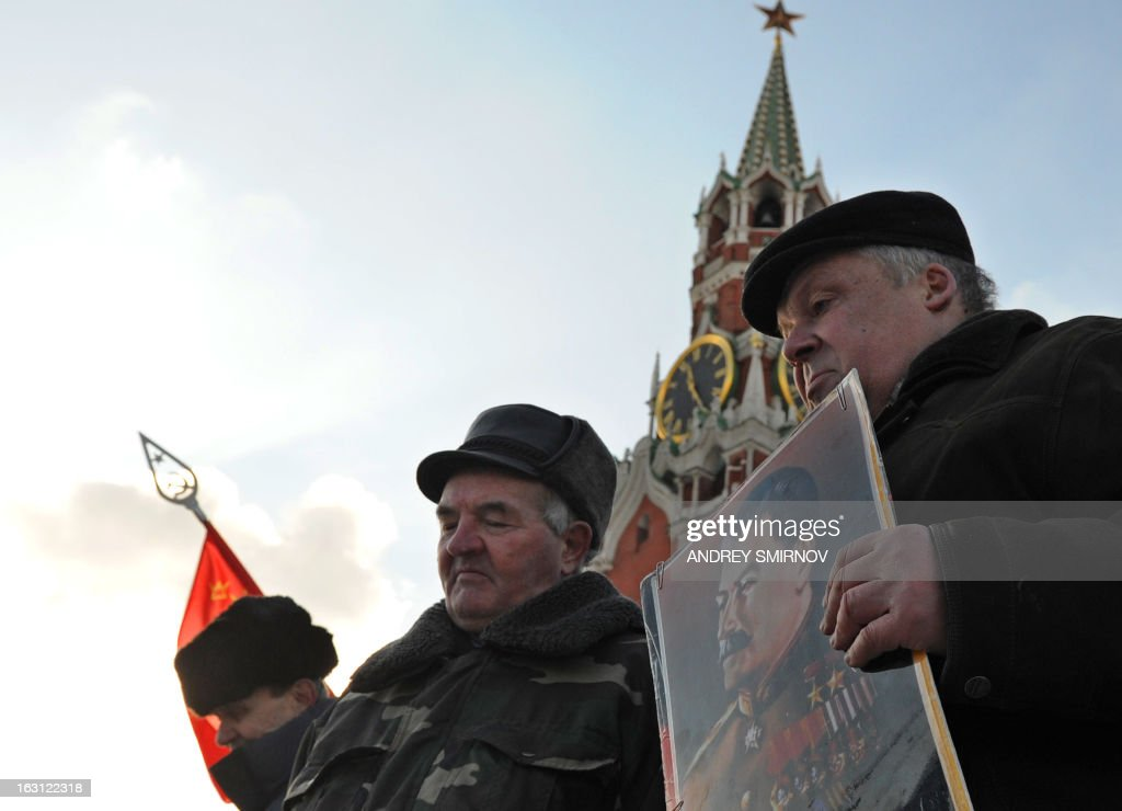 SMIRNOV-- Russian Communists and their supporters carry a portrait of Soviet dictator Josef Stalin as they lay flowers at his tomb at the Red Square in Moscow on March 5, 2013, to mark the 60th anniversary of Stalin's death. Russia marks today 60 years since the death of Stalin with attitudes split about whether to view him as a tyrant who slaughtered millions or a national saviour who helped turn the country into a global superpower that emerged victorious in World War II.