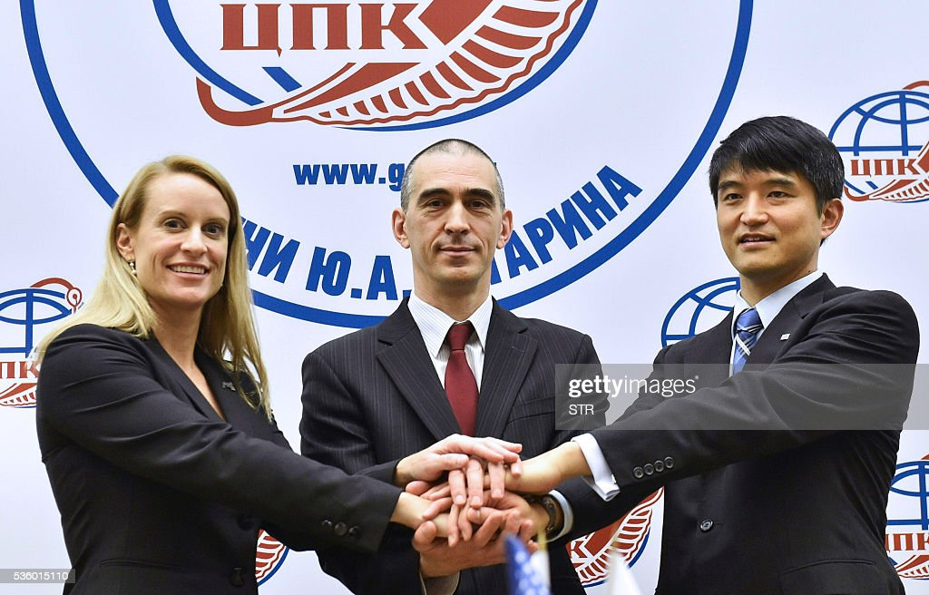 Russian cosmonaut Anatoli Ivanishin (C), Japanese JAXA astronaut Takuya Onishi (R) and US NASA astronaut Kate Rubins pose during a press conference at the Gagarin Cosmonauts Training Centre in Star City, outside Moscow, on May 31, 2016. The trio is to take off from Kazakhstan's Baikonur cosmodrome to the International Space Station (ISS) on June 24, 2016. / AFP / Kirill KUDRYAVTSEV