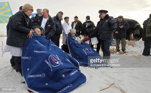 Russian cosmonaut Maxim Surayev and US astronaut Jeffrey Williams sit wrapped in blue blankets after landing in Russian 'Soyuz TMA16' space capsule...