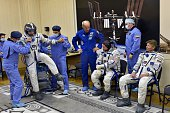 Russian cosmonaut Mikhail Kornienko tests his space suit and US astronaut Scott Kelly and Russian cosmonaut Gennady Padalka wait for testing at the...