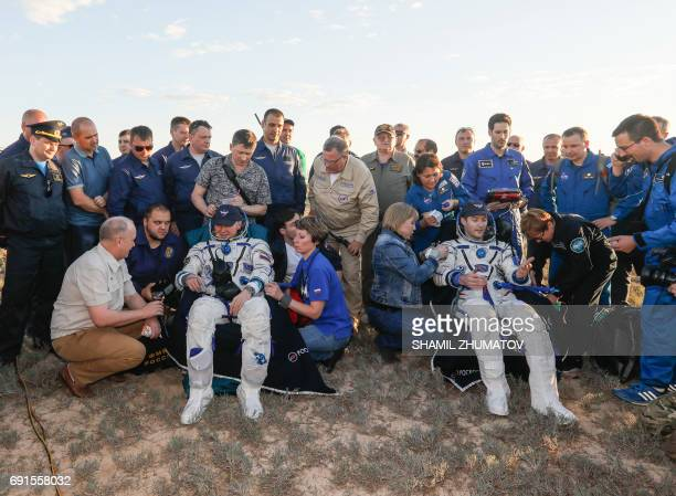TOPSHOT Russian cosmonaut Oleg Novitskiy and French astronaut Thomas Pesquet rest in chairs after landing in a remote area outside the town of...
