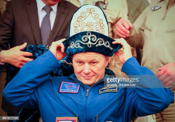 Russian cosmonaut Oleg Novitskiy is presented with a traditional Kazakh hat during a press conference at the airport in Karaganda Kazakhstan on June...
