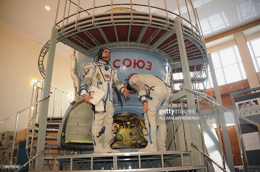 Russian cosmonaut Pavel Vinogradov (L) and US astronaut Christopher Cassidy (R) stand in front of a mock-up of a Soyuz TMA space craft at the cosmonaut training centre in Star City, outside Moscow on March 5, 2013. The three-man crew is scheduled to blast off to the International Space Station (ISS) from the Russian leased Kazakhstan's Baikonur cosmodrome on March 28.