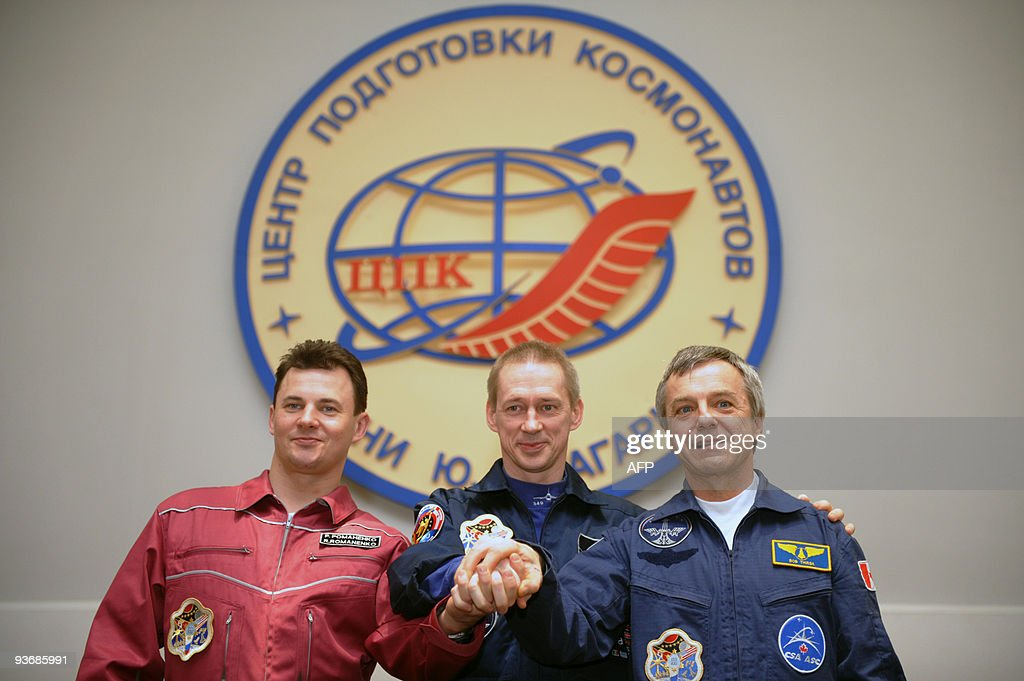 Russian cosmonaut Roman Romanenko (L), European Space Agency (ESA) astronaut Frank de Winne of Belgium (C) and Canadian astronaut Robert Thirsk (R) clasp hands during a press conference outside Moscow in Star City on December 3, 2009. The Russian Soyuz space capsule, carrying Belgian Frank de Winne, Canadian Robert Thirsk and Russian Roman Romanenko, landed as planned at 10:17 a.m. Moscow time (0717 GMT) on November 1 about 85 km (50 miles) north of the town of Arkalyk in Kazakhstan.