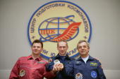 Russian cosmonaut Roman Romanenko European Space Agency astronaut Frank de Winne of Belgium and Canadian astronaut Robert Thirsk clasp hands during a...