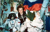 Russian cosmonaut Serguei Avdeyev center poses for a photo December 31 1995 aboard the Mir space station with his space suited colleagues Yuri...