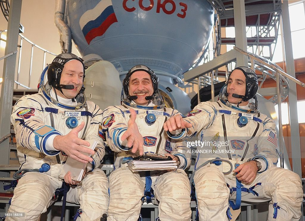 Russian cosmonauts, Pavel Vinogradov (C), Alexander Misurkin (L), and US astronaut Christopher Cassidy join their hands in front of a mock-up of a Soyuz TMA space craft at the cosmonaut training centre in Star City, outside Moscow on March 5, 2013, before taking their pre-flight exam. The three-man crew is scheduled to blast off to the International Space Station (ISS) from the Russian leased Kazakhstan's Baikonur cosmodrome on March 28.