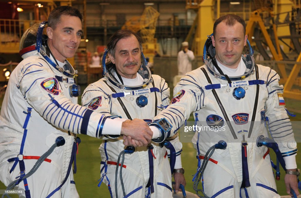 Russian cosmonauts, Pavel Vinogradov (C), Alexander Misurkin (R), and US astronaut Christopher Cassidy (L) join their hands as they take part in a pre-flight training at the Russian leased Kazakhstan's Baikonur cosmodrome on March 17, 2013. The three-man crew is scheduled to blast off to the International Space Station (ISS) from Baikonur on March 29.