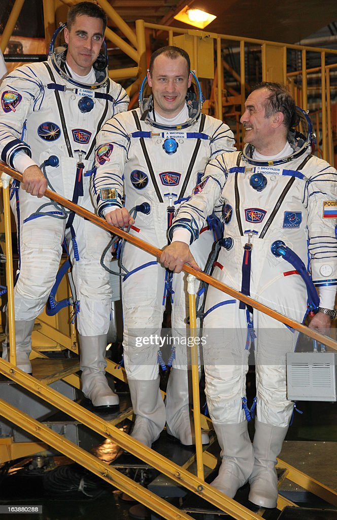 Russian cosmonauts, Pavel Vinogradov (R), Alexander Misurkin (C), and US astronaut Christopher Cassidy (L) pose for a photo as they take part in a pre-flight training at the Russian leased Kazakhstan's Baikonur cosmodrome on March 17, 2013. The three-man crew is scheduled to blast off to the International Space Station (ISS) from Baikonur on March 29. PHOTO