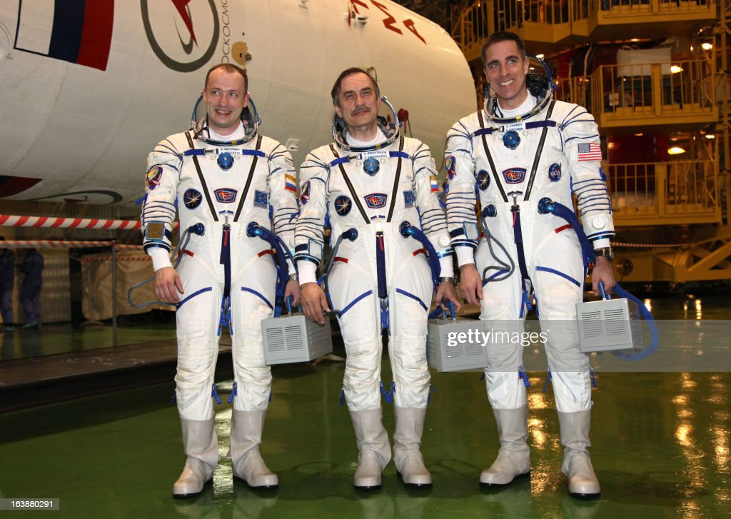 Russian cosmonauts, Pavel Vinogradov (C), Alexander Misurkin (L), and US astronaut Christopher Cassidy (R) pose for a photo as they take part in a pre-flight training at the Russian leased Kazakhstan's Baikonur cosmodrome on March 17, 2013. The three-man crew is scheduled to blast off to the International Space Station (ISS) from Baikonur on March 29. PHOTO