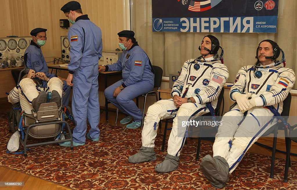 Russian cosmonauts, Pavel Vinogradov (R), Alexander Misurkin (L), and US astronaut Christopher Cassidy (2nd R) take part in a pre-flight training at the Russian leased Kazakhstan's Baikonur cosmodrome on March 17, 2013. The three-man crew is scheduled to blast off to the International Space Station (ISS) from Baikonur on March 29. PHOTO