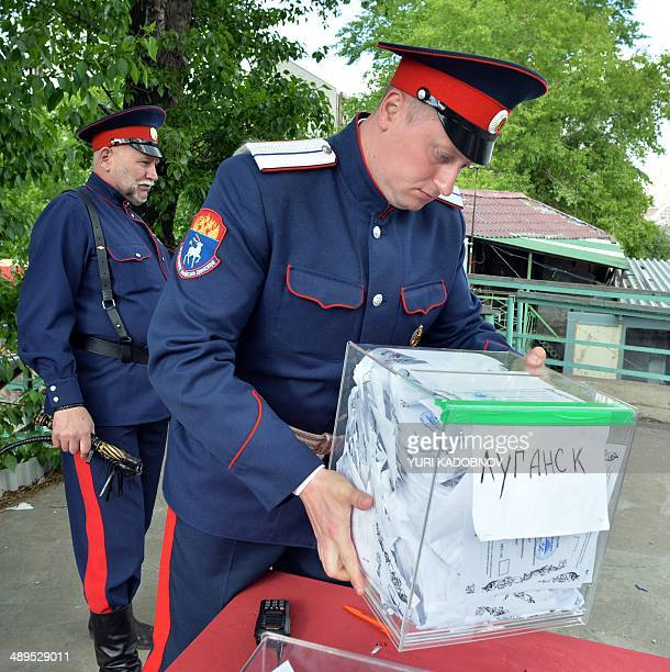 A Russian cossack wearing his military uniform carries a ballot box reading 'Luhansk' at a polling station in Moscow on May 11 2014 Voting opened...