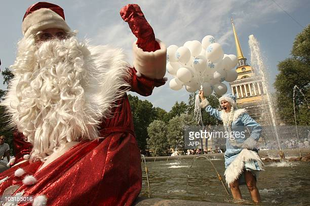 A Russian couple dressed as Father Frost and a snow princess stand in a fountain in central Saint Petersburg on July 28 2010 to take people's minds...