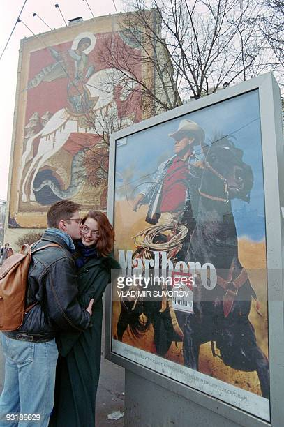 A Russian couple kisses on November 17 1995 in front of two advertising billboards with horseback riders a Marlboro cowboy cigarette poster and an...
