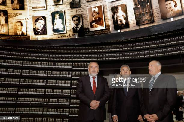 Russian Defence Minister Sergei Shoigu looks at pictures of Jewish Holocaust victims at the Hall of Names as he stands next to his Israeli...