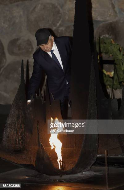 Russian Defence Minister Sergei Shoigu rekindles the eternal flame at the Hall of Remembrance on October 17 2017 during his visit to the Yad Vashem...