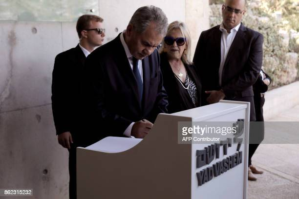 Russian Defence Minister Sergei Shoigu signs the guest book on October 17 2017 during his visit to the Yad Vashem Holocaust Memorial museum in...