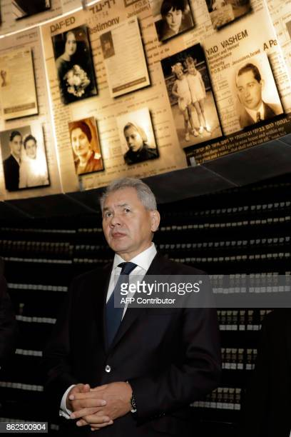 Russian Defense Minister Sergei Shoigu looks at pictures of Jewish Holocaust victims at the Hall of Names on October 17 2017 during his visit to the...