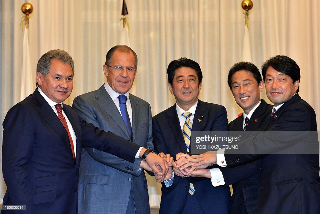 Russian Defense Minister Sergei Shoigu, Russian Foreign Minister Sergey Lavrov, Japanese Prime Minister Shinzo Abe, Japanese Foreign Minister Fumio Kishida and Japanese Defense Minister Itsunori Onodera shake hands prior to their meeting at the prime minister's residence in Tokyo on November 2, 2013. AFP PHOTO / POOL / Yoshikazu TSUNO