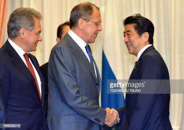Russian Defense Minister Sergei Shoigu watches as Russian Foreign Minister Sergey Lavrov shakes hands with Japanese Prime Minister Shinzo Abe prior...