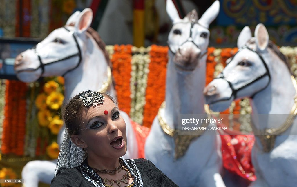 A Russian devotee of the International Society of Krishna Conciousness (ISKON) performs a traditional Indian devotional dance as she waits to pull the holy rope of the Chariot of Lord Jagannath during the Rath Yatra celebration in Kolkata on July 10, 2013. According to mythology, the Ratha Yatra dates back some 5,000 years when Hindu god Krishna, along with his older brother Balaram and sister Subhadra, were pulled on a chariot from Kurukshetra to Vrindavana by Krishna's devotees. AFP PHOTO/Dibyangshu SARKAR