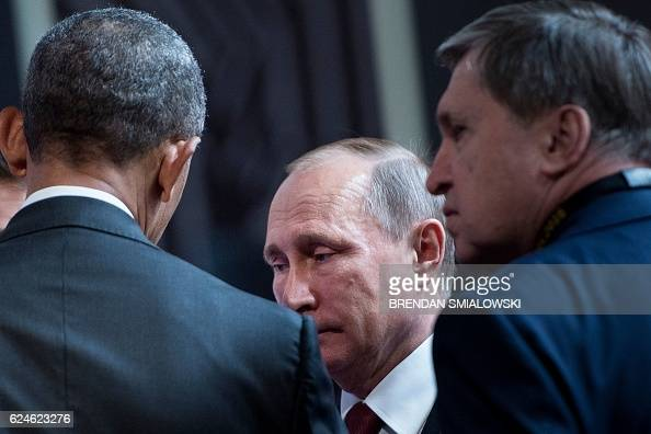 Russian diplomat Yuri Ushakov listens while US President Barack Obama and Russia's President Vladimir Putin talk before an economic leaders meeting...
