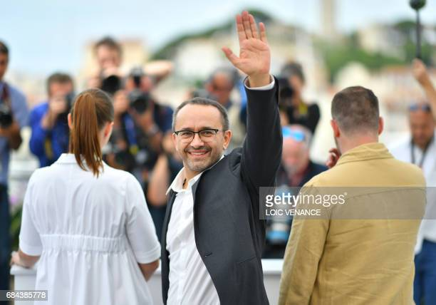 Russian director Andrey Zvyagintsev waves while posing on May 18 2017 with Russian actress Maryana Spivak and Russian actor Alexey Rozin during a...