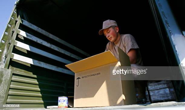 A Russian driver opens a box containing condensed milk inside a truck of Russian humanitarian convoy parked in a field outside the town of...