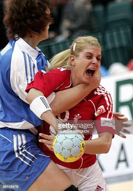 Russian Elena Polenova blocks Danish Rikke Horlykke Jorgensen during their semifinal handball match of the XVII Women's World Championship in St...