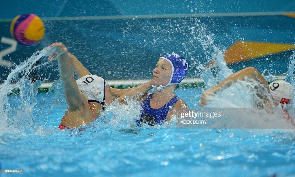 Russian Evgeniya Ivanova is challenged by China's Na Huaanhuan and Wang Yi during the women's water polo Classification 5th/8th round match at the...