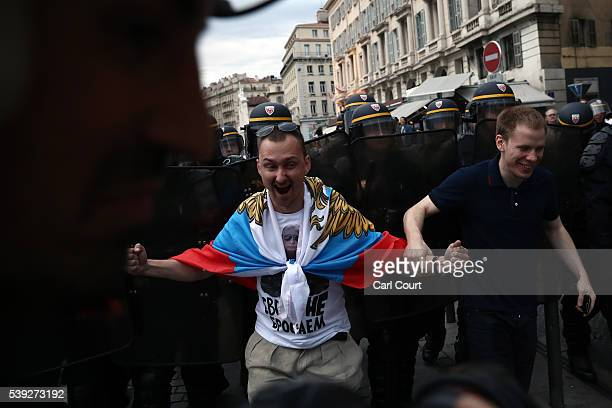 Russian fan gestures in front of police officers as England fans clash with police in Marseille on June 10 2016 in Marseille France Football fans...