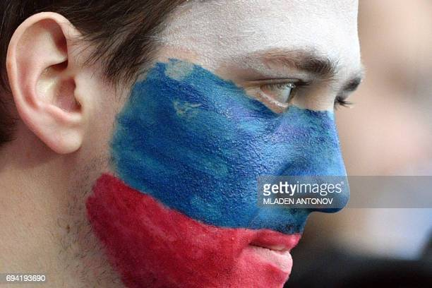 A Russian fan watches a friendly football match between Russia and Chile at the CSKA Arena in Moscow on June 9 2017 / AFP PHOTO / Mladen ANTONOV