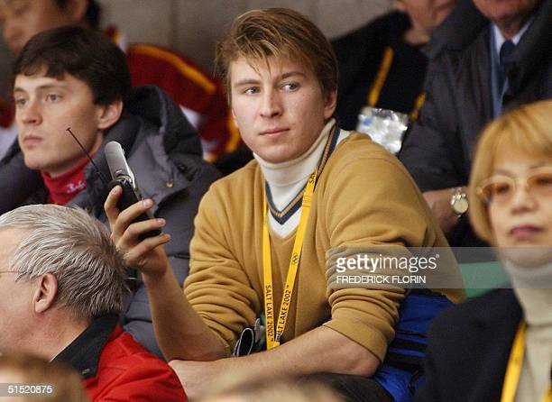 Russian figure skater Alexei Yagudin gold medalist of the olympic men's figure skating competition gives a phonecall as he watches the women's free...