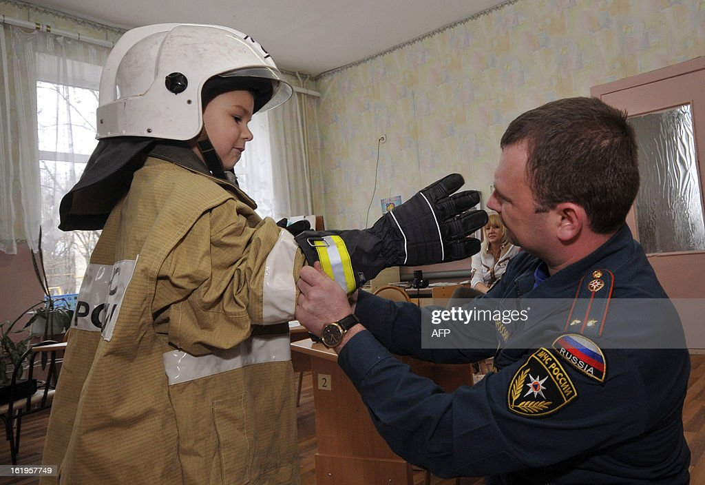 A Russian firefighter dresses a boy in a firefighter's uniform during a fire training, in a kindergarten in the town of Nevinnomyssk, some 60 kilometers from the southern Russian city of Stavropol, on February 18, 2013. AFP PHOTO / DANIL SEMYONOV