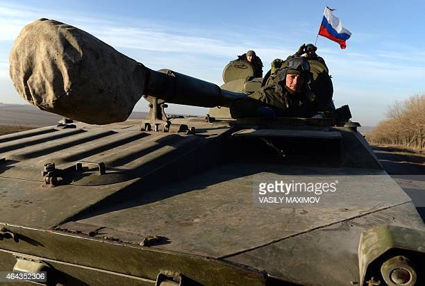 A Russian flag flies near ProRussia militants sitting atop a 2S1 Gvozdika as a convoy of proRussian forces takes a break as they move from the...