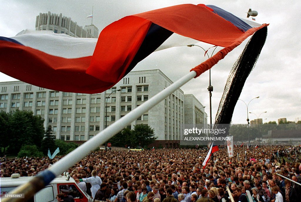 A Russian flag is waved above people taking part in a funeral procession for the victims of the coup in front of the Russian White House in Moscow on...