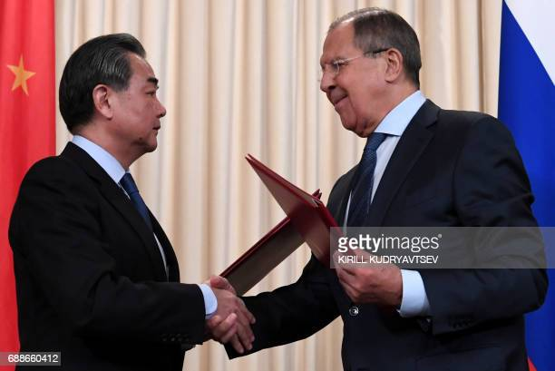 TOPSHOT Russian Foreign Minister Sergei Lavrov and his Chinese counterpart Wang Yi exchange documents during a joint press conference following their...