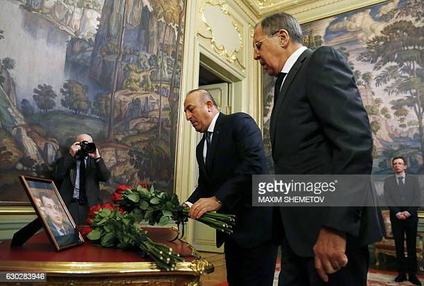 Russian Foreign Minister Sergei Lavrov and his Turkish counterpart Mevlut Cavusoglu lay flowers in front of a photo of Russian ambassador to Turkey...