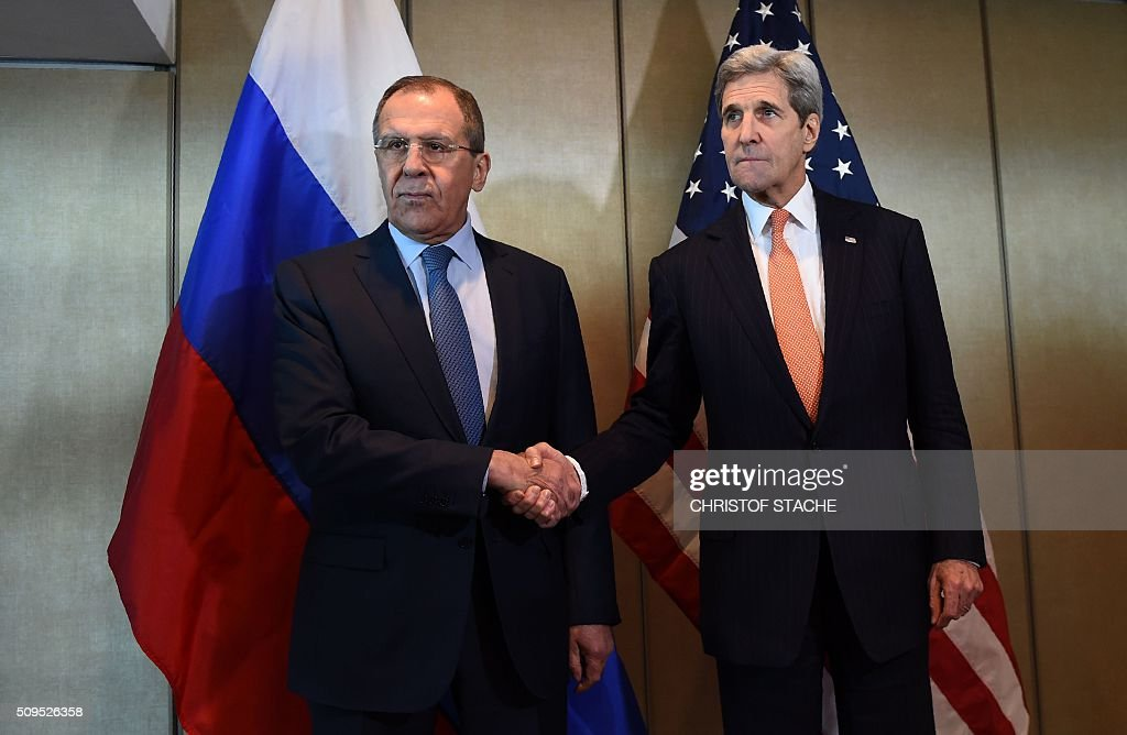 Russian Foreign Minister Sergei Lavrov (L) and US Secretary of States John Kerry shake hands as they meet for diplomatic talks on February 11, 2016 in Munich, southern Germany. Russia said it was ready to discuss a ceasefire in Syria as foreign ministers gathered in Munich in a bid to kick-start peace talks derailed by the regime onslaught on the besieged city of Aleppo. / AFP / Christof STACHE