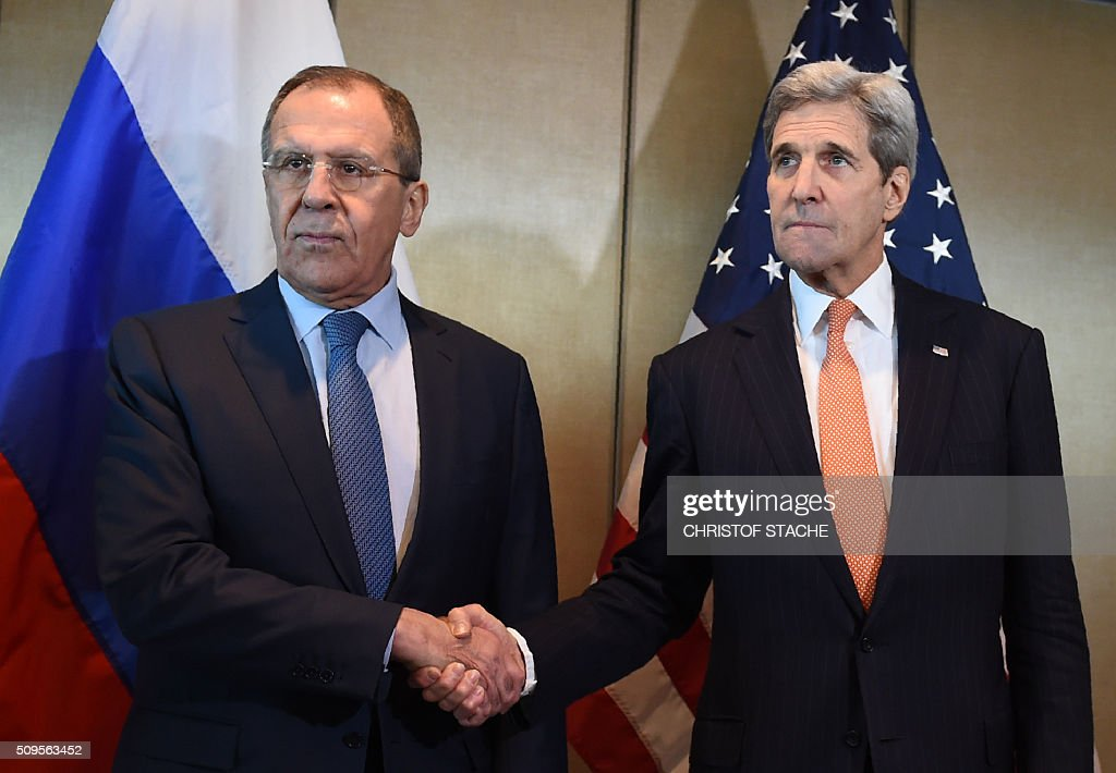 CROP - Russian Foreign Minister Sergei Lavrov (L) and US Secretary of States John Kerry shake hands as they meet for diplomatic talks on February 11, 2016 in Munich, southern Germany. Russia said it was ready to discuss a ceasefire in Syria as foreign ministers gathered in Munich in a bid to kick-start peace talks derailed by the regime onslaught on the besieged city of Aleppo. / AFP / Christof STACHE